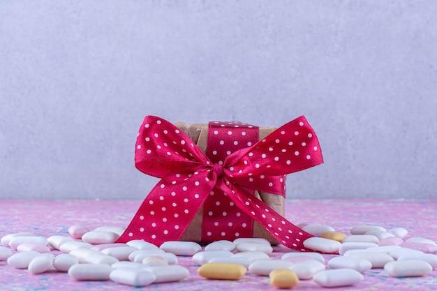 Geschenkpakket in het midden van een verspreide bundel kauwgums op een kleurrijk oppervlak