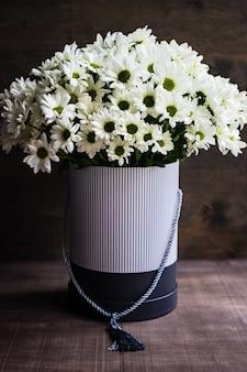 Geschenksamenstelling met verse seizoenswitte daisylbloemen in doos