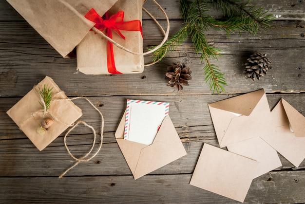 Geschenkverpakking en brieven, kaarten voor kerstgroet. enveloppen met brieven, geschenken, kerstboom takken en kegels, bovenaanzicht, kopie ruimte