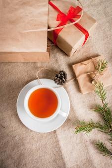 Geschenkverpakking en brieven, kaarten voor kerstgroet. enveloppen met brieven, geschenken, kerstboomtakken en dennenappels liggen op een houten tafel liggen, een kopje geurige hete thee, bovenaanzicht