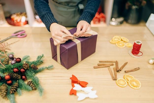 Geschenkverpakking en decoratie, handgemaakte verpakking. vrouw wraps aanwezig op tafel, decorprocedure