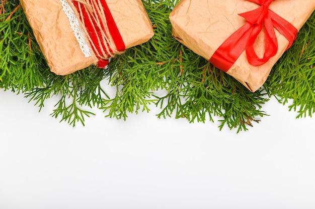 Geschenkverpakking gemaakt van papier op een witte ruimte. groene takken. plaats om te schrijven. uitzicht van boven. handgemaakte eenvoudige kerstcadeau lege bovenaanzicht ruimte. geschenkdoos, kerstboom.