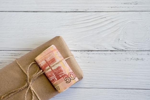 Geschenkverpakking in ambachtelijk papier met geld. russische roebels. geld cadeau.