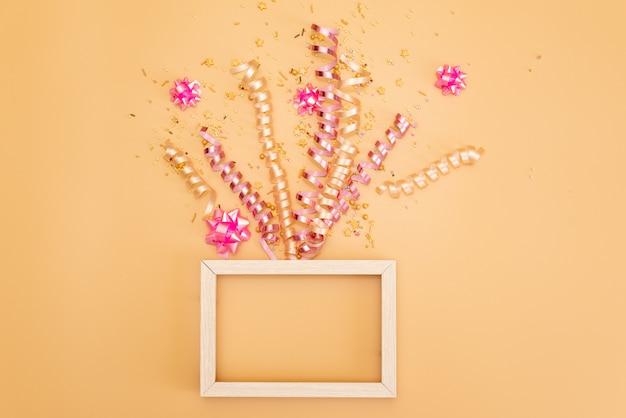 Geschenkverpakking met diverse feest confetti, streamers, noisemakers en decoratie op een oranje achtergrond.