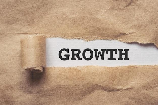 Gescheurd bruin papier op witte achtergrond met groei erop geschreven written