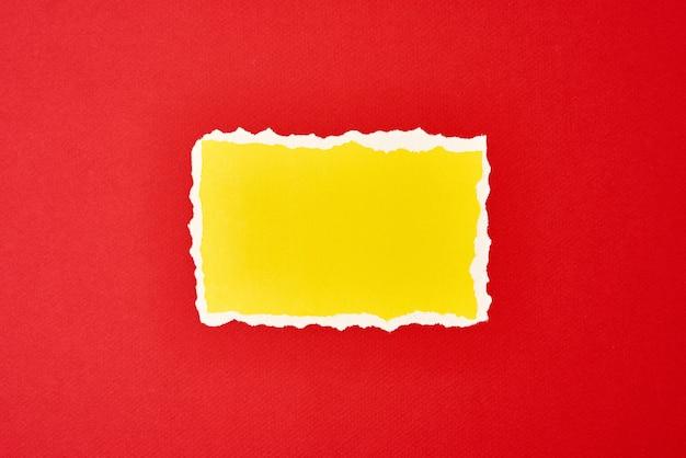 Gescheurd geel papier gescheurd randblad op rode achtergrond. sjabloon met stuk gekleurd papier