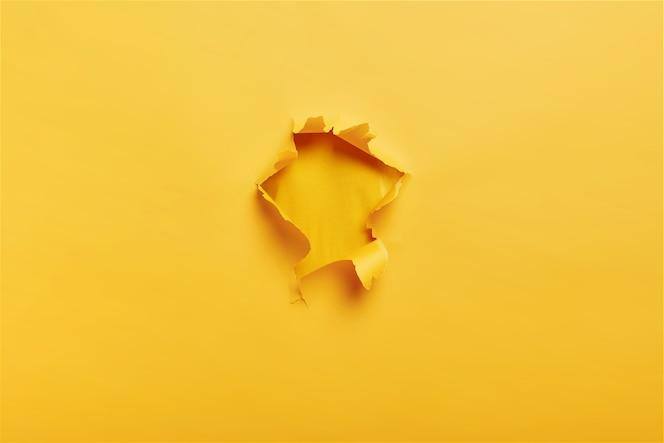 Gescheurd geel papier met gat in het midden