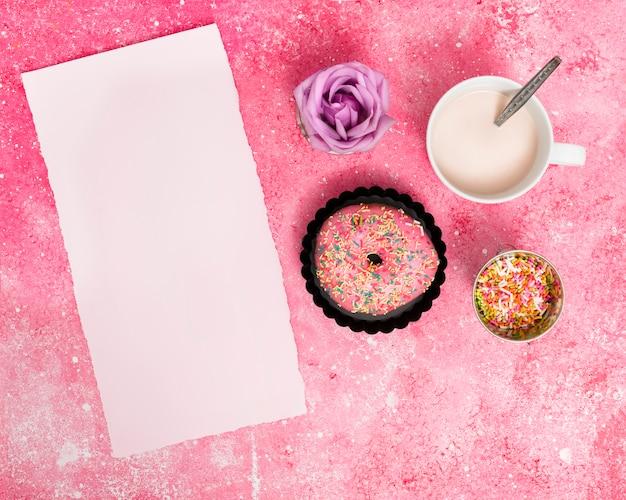 Gescheurd leeg witboek met hagelslag; donut; roos en melk tegen roze gestructureerde achtergrond