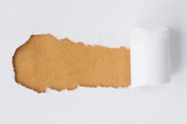 Gescheurd papier dat karton onthult