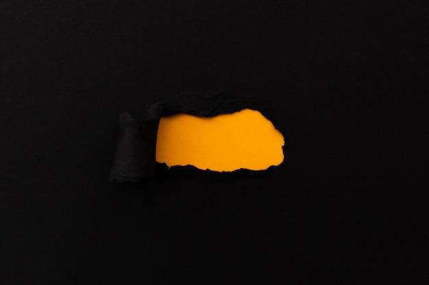 Gescheurd papier met lege ruimte voor uw bericht. zwart gescheurd papier met oranje achtergrond
