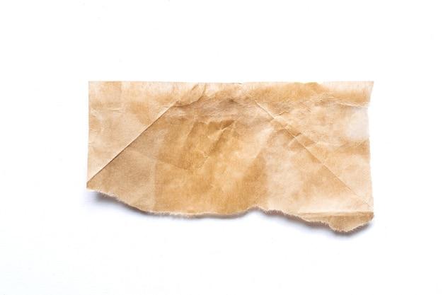 Gescheurd stuk bruin papier op een witte achtergrond