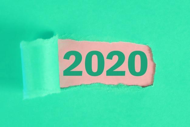 Gescheurd stuk papier onthullend woord nieuwjaar 2020.