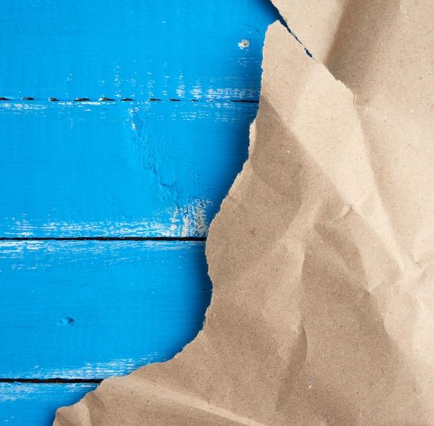 Gescheurd stuk papier op blauwe houten achtergrond