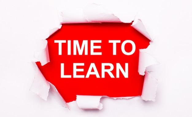 Gescheurd wit papier ligt op een rode achtergrond. op rood is de tekst wit time to learn