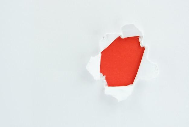 Gescheurd wit papier tegen een rode achtergrond