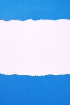 Gescheurde blauw papier witte achtergrond grenskader verticaal