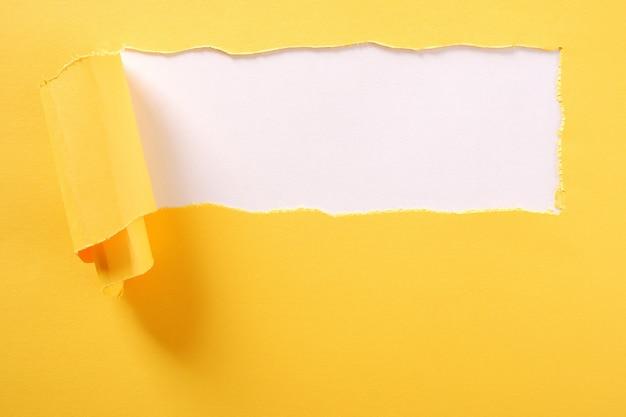 Gescheurde gele papieren strook witte achtergrond geript