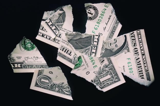 Gescheurde gescheurde gedevalueerde bankbiljet van één dollar op een zwarte ondergrond.