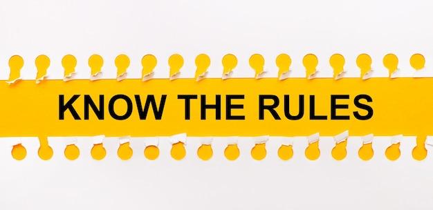 Gescheurde papieren strook op gele achtergrond met tekst know the rules