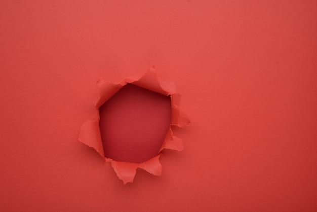 Gescheurde rode papier muur achtergrond. kopieer ruimte opzij voor uw reclame- en aanbod- of verkoopinhoud.