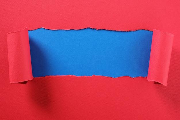 Gescheurde rode papieren strook gekrulde rand onthullend midden