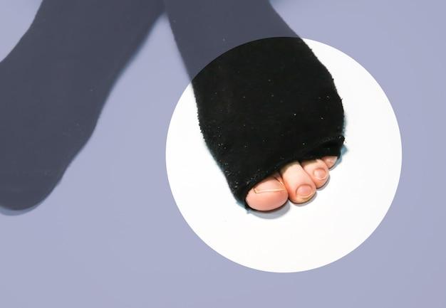 Gescheurde sokken aan de voeten van de mens. sjofele kleding. arm persoon.