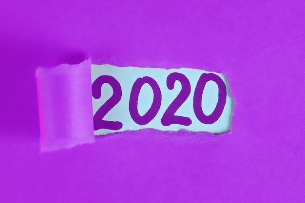 Gescheurde stuk papier onthullende woord nieuwjaar 2020.