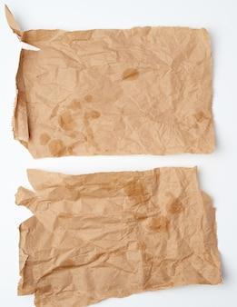 Gescheurde verfrommelde stukjes bruin papier met vetvlekken