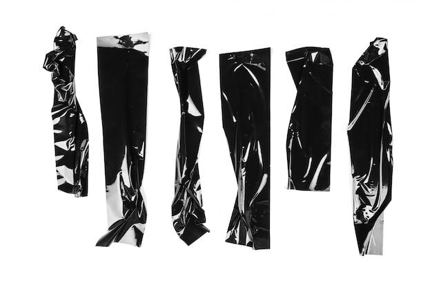 Gescheurde zwarte plakband van verschillende grootte, zelfklevende stukken