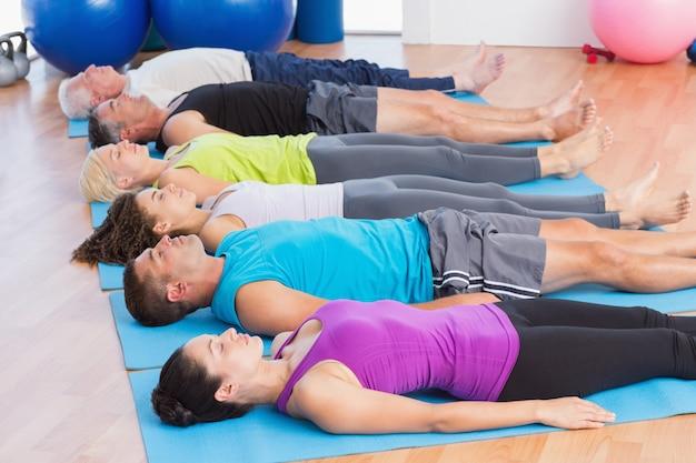 Geschikt mannen en vrouwen die op oefeningsmatten in geschiktheidsclub mediteren