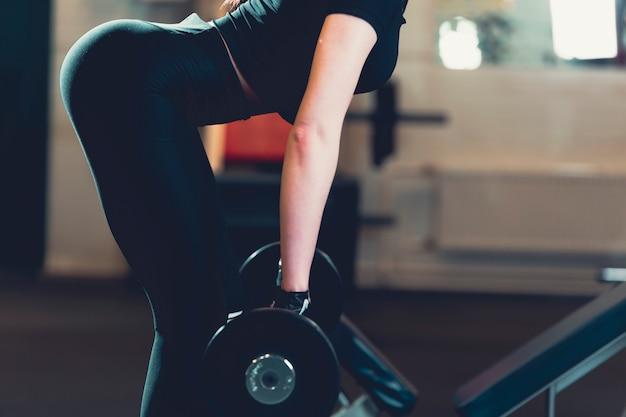 Geschikt vrouw het opheffen gewicht in gymnastiek