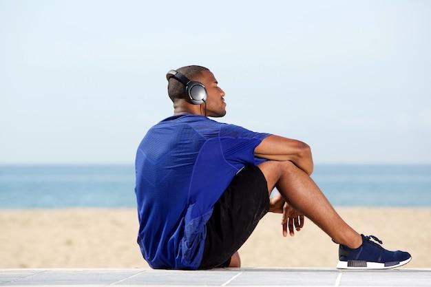 Geschikte afrikaanse mens die aan muziek bij strand luisteren