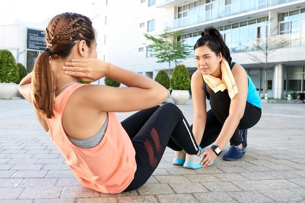Geschikte aziatische vrouw die sit-ups op bestrating in straat en vriend doet die haar voeten houdt