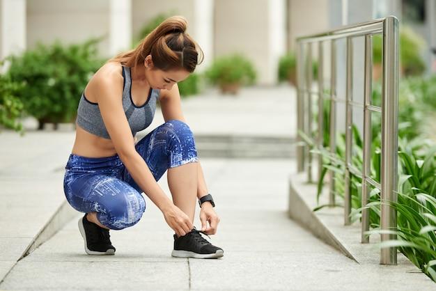 Geschikte aziatische vrouw in sportkleding die schoenveters in straat binden