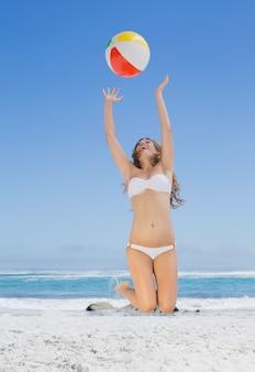 Geschikte blonde in witte bikini die strandbal op een zonnige dag werpt