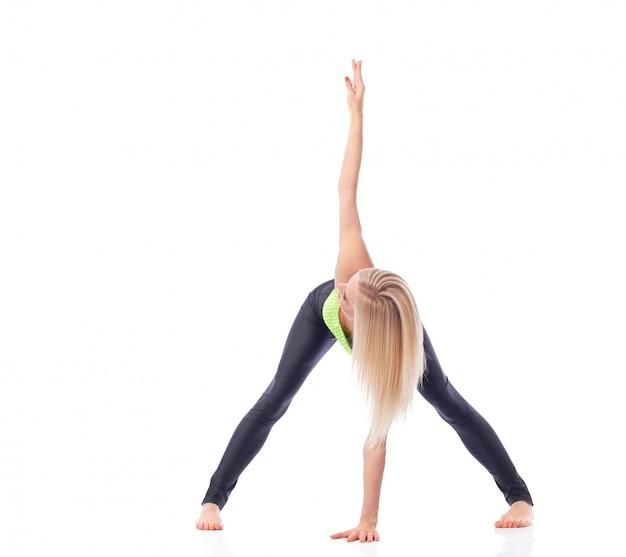 Geschikte en actieve jonge vrouw die het achter uitrekken uitvoeren die yogaasana doen