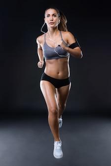 Geschikte en sportieve jonge vrouw die over zwarte achtergrond loopt.