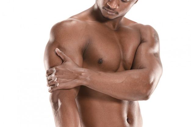 Geschikte jonge mens met mooi die torso op wit wordt geïsoleerd