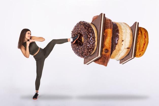Geschikte jonge vrouw die nee zegt tegen snoep, snoep en koolhydraten