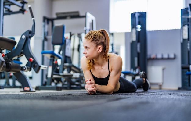 Geschikte jonge vrouw die op de vloer ligt en maagoefeningen doet bij sportclub.