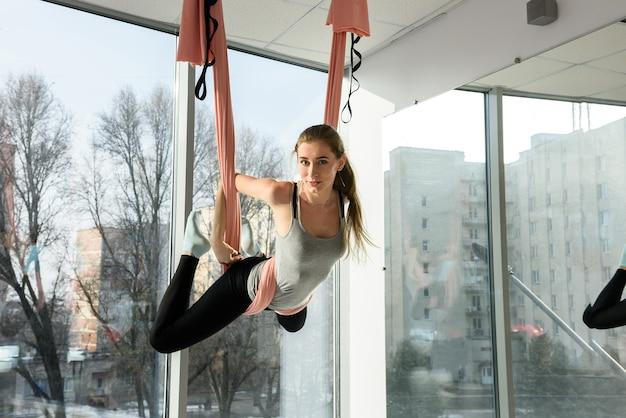 Geschikte jonge vrouw die sportwear draagt die vliegyoga doet