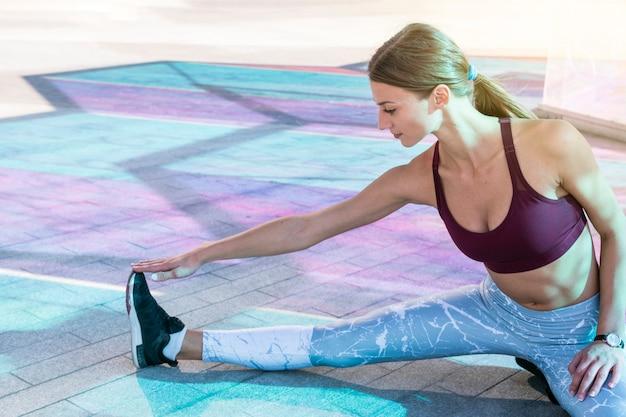 Geschikte jonge vrouw die uitrekkende training op de vloer doet
