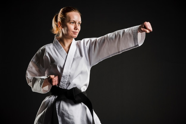 Geschikte karatevrouw die middelgroot schot uitoefenen