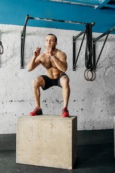 Geschikte mens die doossprongen in een gymnastiek doet