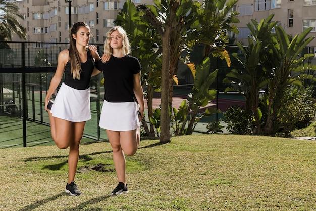 Geschikte tennisspelers die volledig schot uitrekken
