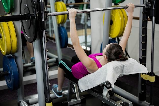 Geschikte vrouw die de barbellbankpers in gymnastiek opheffen