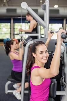 Geschikte vrouw die gewichtsmachine in gymnastiek met behulp van