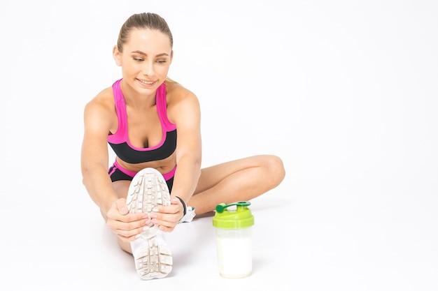 Geschikte vrouw die haar been uitrekt om op te warmen - dat over witte achtergrond wordt geïsoleerd