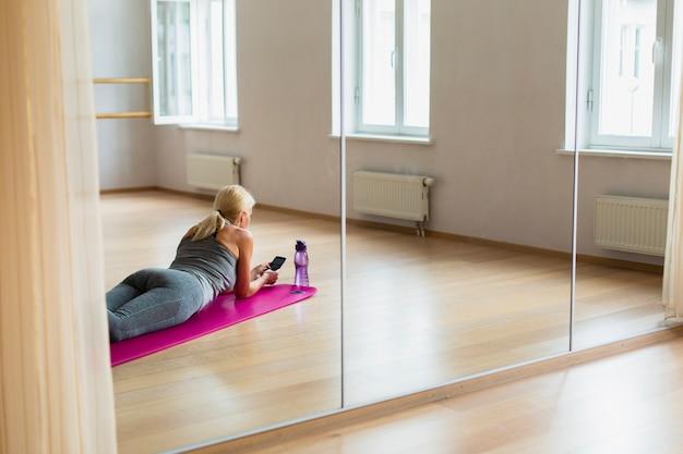 Geschikte vrouw die haar telefoon controleert bij de gymnastiek