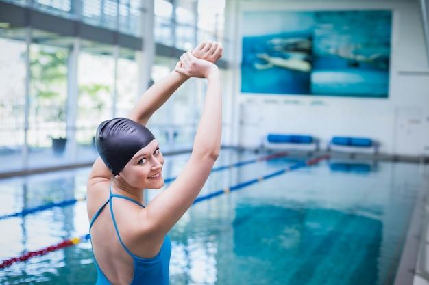 Geschikte vrouw die haar wapens uitrekt bij de pool